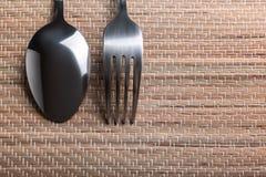 Forchetta e cucchiaio sulla tovaglia, paglia Immagini Stock