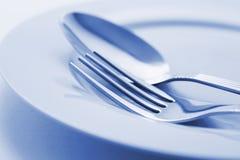 Forchetta e cucchiaio sulla zolla Immagini Stock