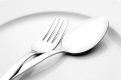 Forchetta e cucchiaio sulla zolla bianca Fotografia Stock Libera da Diritti