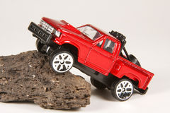 Ford 4x4 Pickup Climbing a Rock. Maisto 3 die-cast toy Ford 4x4 Pick-Up Truck climbing a rock Royalty Free Stock Photos