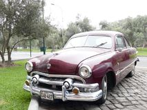 Ford Custom V8 two-door maroon color in Lima. Lima, Peru. October 14, 2017. Front and side view of a maroon Ford Custom V8 two-door built by Ford Motor Company royalty free stock photos
