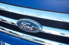 Ford-Logo auf einem blauen Auto mit Reflexion chromiert an Stockbild