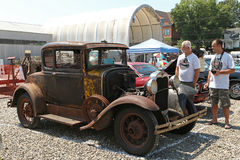 1930 Ford Model A. MILFORD, CT, USA - AUGUST 15, 2015: Unidentified spectators examine a rusty 1930 Ford Model A on display at a classic car show. The vehicle Stock Photos