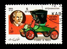 Ford Model A two-seater (1903) and Henry Ford, Motor cars serie, circa 1984. MOSCOW, RUSSIA - DECEMBER 21, 2017: A stamp printed in Afghanistan shows Ford Model royalty free stock photo