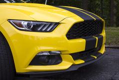 2015 Ford Mustang Coupe Front End. Closeup of bright yellow 2015 Ford Mustang front nose. Black racing stripes across the front end and hood stock photography