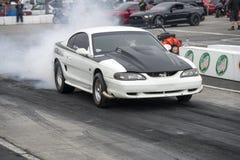 Ford-Mustang, der einen Rauch darstellen lässt auf der Bahn lizenzfreies stockbild