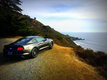 Ford Mustang driving up California Coastline Royalty Free Stock Images