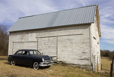 1951 Ford Sedan by Old White Barn. 1951 Ford Custom Sedan parked in front of an old white barn.  This barn was built circa 1890-1900 Royalty Free Stock Photos