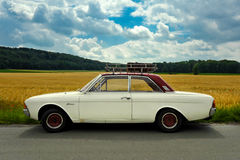 Ford Taunus youngtimer with roof rack and case in front of a corn field. White/ Red Stock Images