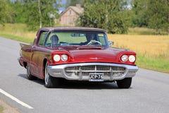Ford Thunderbird Hardtop rojo 1960 en el camino Imágenes de archivo libres de regalías
