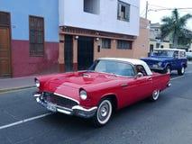 Ford Thunderbird rojo y blanco y Ford Bronco azul y blanco que va a una exposición en el distrito de Libre del pueblo de Lima Imágenes de archivo libres de regalías