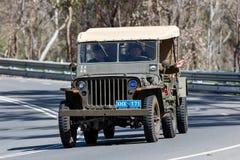 Ford Willys Jeep 1943 que conduz na estrada secundária imagem de stock