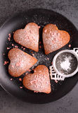 Fore cupcakes in heart with powdered sugar on a black plate. Valentines day Stock Images