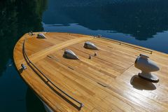 Fore part of a rarity wooden boat against the background of the clear water of the lake.  Stock Photo