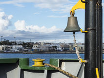 Fore ship of a vessel with ship bell. Fore ship of a vessel lying at the pier with harbor view equipped with ship bell, winch and lashing Stock Image