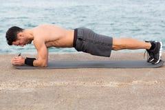 Forearm plank. Exercise outside close to the beach Stock Photos
