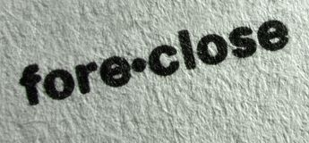 Foreclose. Extreme macro of the typed word foreclose on a piece of paper stock photography