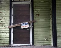 Foreclosed house. An old vacant house with Foreclosure sign on door Royalty Free Stock Image