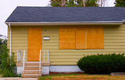 Foreclosure. A house in good condition with the door and windows boarded up with plywood Stock Photo