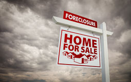 Foreclosure Home For Sale Real Estate Sign. White and Red Foreclosure Home For Sale Real Estate Sign Over Ominous Cloudy Sky stock photos
