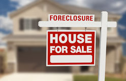 Foreclosure House For Sale Sign and House. Foreclosure House For Sale Sign in Front of Beautiful Home Royalty Free Stock Photography