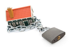 Foreclosure and mortgage concept. House in chains locked with padlock - mortgage and foreclosure concept Stock Photos