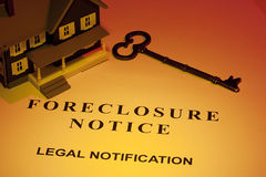 Foreclosure Notice. A key laying next to a house model and a foreclosure notice Stock Photo