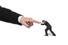 Малый человек нажимая против большого другой forefinger руки Стоковые Фото