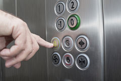 Forefinger pressing the alarm button in the elevator. Man pressing the alarm button in the elevator with his forefinger royalty free stock photos