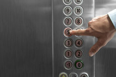 Forefinger pressing the fifth floor button in the elevator. Male forefinger pressing the fifth floor button in the elevator. External flash light. Metal made stock image