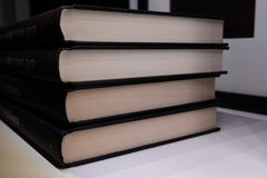 Forefront of a group of books stacked. Forefront of a group of black books stacked stock photos