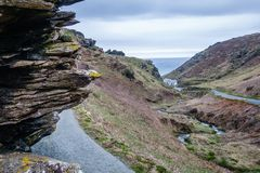 At the forefront is a rock and a narrow path along it. Natural landscape overlooking the valley and the sea; cloudy hiking day; At the forefront is a rock and a royalty free stock photography