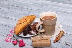 In the foreground a croissant with a chocolate cake, on a gray background, a number of pink petals are next to it, a Stock Photography