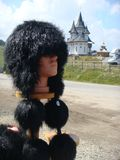 Foreground of a characteristic fur hat of Romania with pompoms to the extremity and  traditional churches in distance. Foreground of a black traditional hat of Royalty Free Stock Images