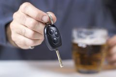 In the foreground car keys kept in a male hand. A beer mug in the background.  royalty free stock photo