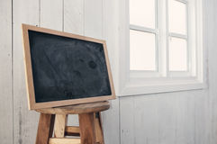 Foreground dirty chalkboard on round wooden chair,  near a white. Windowsill and white wooden wall background Royalty Free Stock Photo