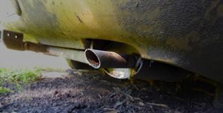 Foreground of an exhaust pipe of a golden car Stock Photos