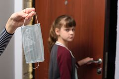 In the foreground, the hand holds a protective medical mask, in the background the girl leaves the house