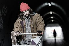 Hopeless drifter with trolley. In the foreground hopeless drifter with trolley looking for shelter in the underpass. Blurred person in the background Royalty Free Stock Images