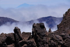The foreground of lava rocks, volcanic mountain and summit of the Teide royalty free stock photos