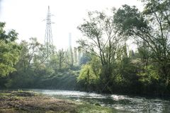 Bucolic landscape with chimney on the background. In the foreground the luxuriant nature, a river among the trees. in the background the chimney of a factory Royalty Free Stock Photo