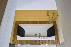 In the foreground a modern bathtub. Recessed in the wooden floor, surrounded by yellow walls royalty free stock images