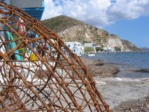 Foreground of a net from fishermen with after all a white village. Island of Milos. Greece. royalty free stock photography