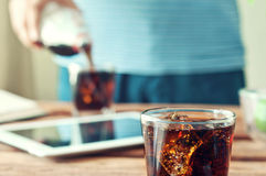 In the foreground poured to the brim glass of cola and ice close. Up. In the background a male hand pour cola into a glass royalty free stock photo