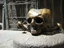 Foreground of a sculpture of a skull and crossbones in front of the church of the purgatory in the center of  Naples . Italy Royalty Free Stock Image