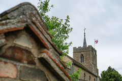 Architectural view of a medieval church tower and spire seen with the English flag flying. Stock Photography