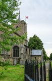 Architectural view of a medieval church tower and spire seen with the English flag flying. Stock Photos