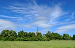Tranquil scene of an old English church seen nestled behind a group of trees in mid summer. The foreground shows a well maintained pasture area used for grazing Stock Photography