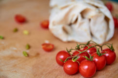 On foreground small cherry tomatoes close up. Vegetarian burrito with vegetables on blurred background Royalty Free Stock Images