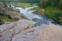 In the foreground, a stone back river with rapids foam water runs out to a quiet place and splits. The landscape of the forest area stock photos